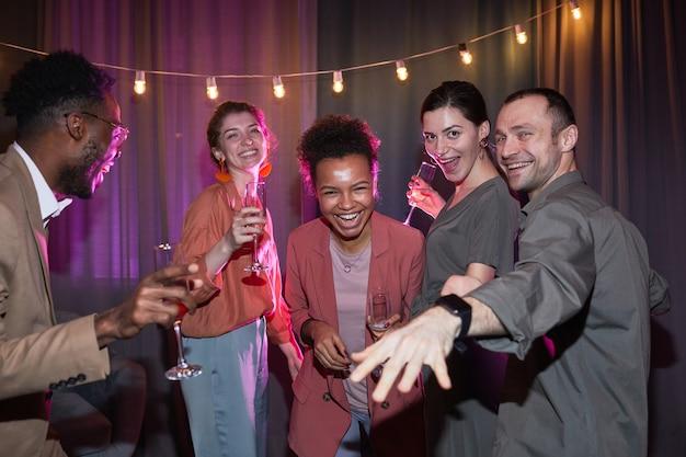 家でパーティーを楽しみながら踊るのんきな人々の多様なグループ、フラッシュで撮影