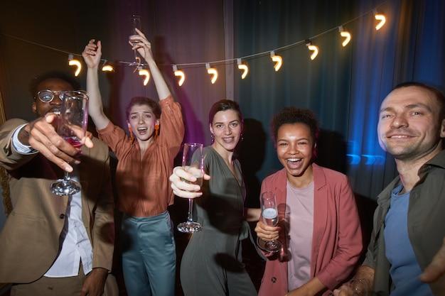 屋内でパーティーを楽しみながら踊るのんきな人々の多様なグループ、フラッシュで撮影