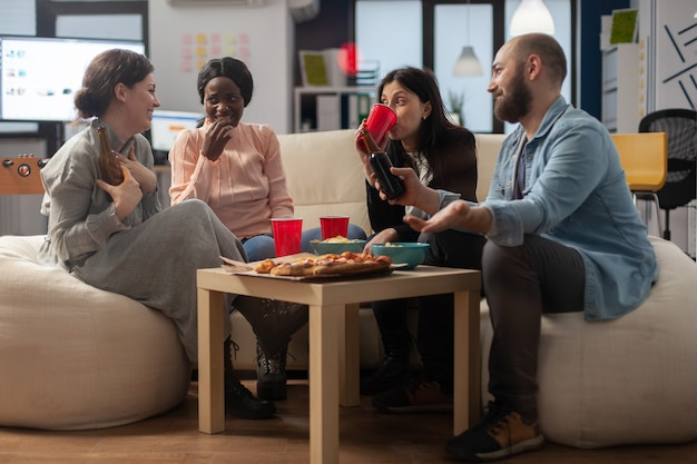 다양한 동료 그룹이 사무실에서 퇴근 후 음료를 즐깁니다. 다양한 인종의 쾌활한 친구들이 소파에 앉아 간식 피자 칩과 테이블에 맥주 알코올 한 병을 들고 있습니다.