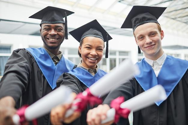 졸업장을 들고 실내에서 카메라를 보며 웃고 있는 다양한 대학 졸업생들