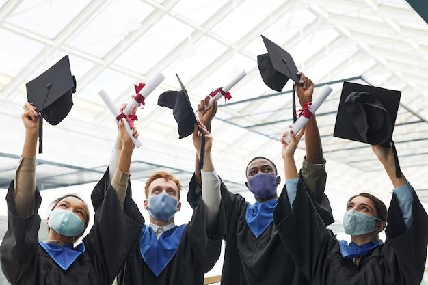Разнообразная группа выпускников колледжа кидает шляпы в воздух и в масках во время выпускной церемонии в помещении, копия пространства