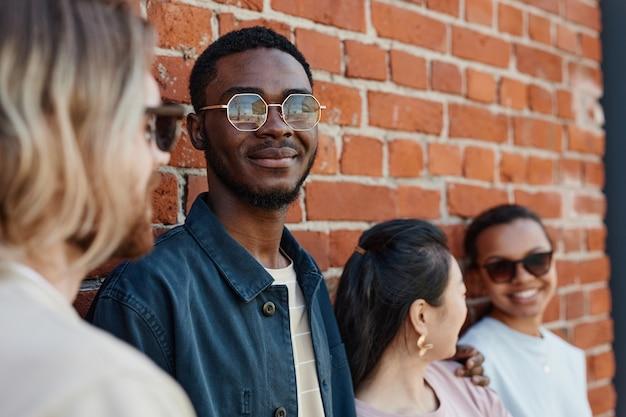 다양한 현대 젊은이들이 야외에서 포즈를 취하며 도시 환경에서 벽돌 벽 옆에 서서 선글라스를 끼고 웃고 있는 아프리카계 미국인 남성에 초점을 맞춥니다.