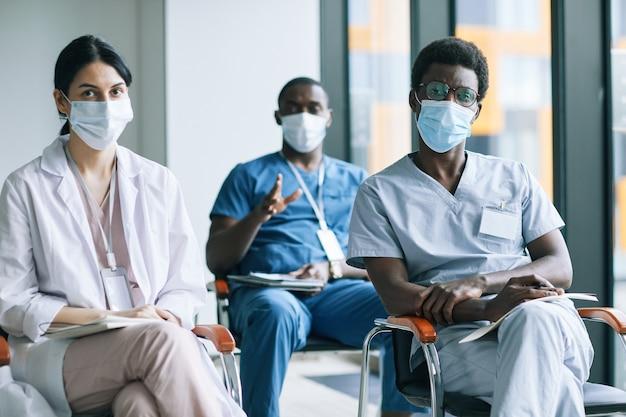 의료 회의나 세미나에 참석하는 동안 마스크를 쓴 다양한 의사 그룹