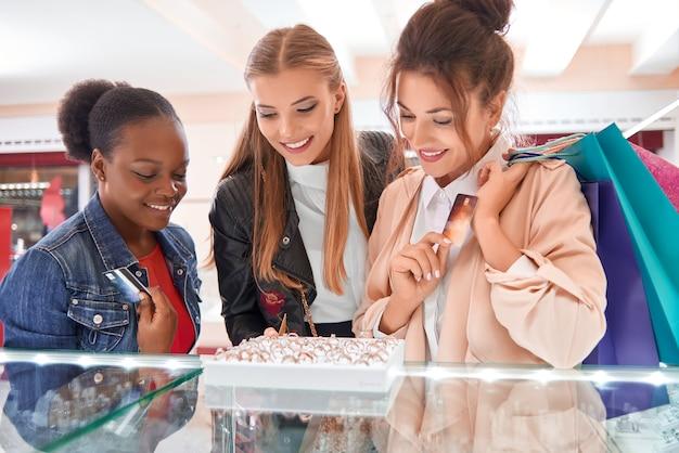 보석을 함께 쇼핑하는 동안 흥분된 여자 친구의 다양한 그룹