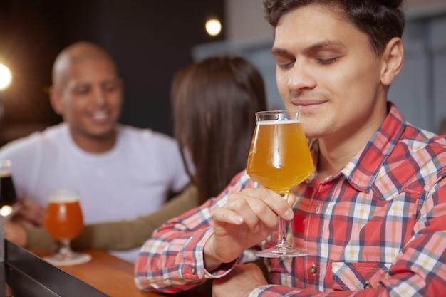 Разнообразная группа друзей, пьющих пиво в пабе вместе
