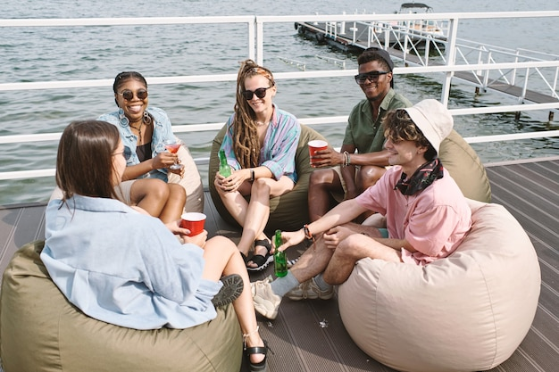 Разнообразная группа друзей, наслаждающихся совместным времяпровождением, сидя на пирсе, выпивая и разговаривая