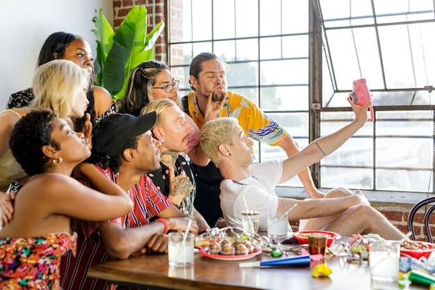 パーティーで自分撮りをしている友達の多様なグループ