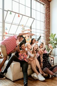 Разнообразная группа друзей, делающих селфи на вечеринке
