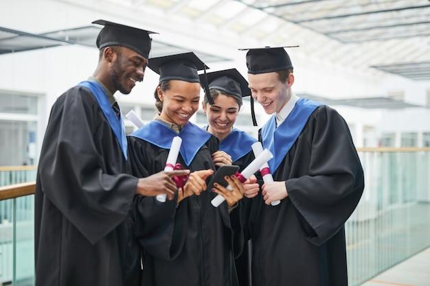 대학 내부에 서 있는 동안 졸업 가운을 입고 스마트폰을 사용하는 다양한 행복한 젊은이들
