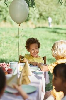 여름에 생일 파티를 위해 풍선으로 장식된 야외 피크닉 테이블에 있는 다양한 아이들