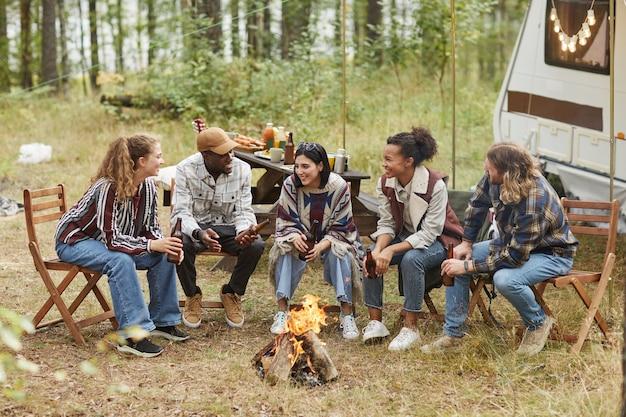 屋外でのキャンプを楽しんだり、ビールの警官を飲みながら火のそばに座ったりする現代の若者の多様なグループ...