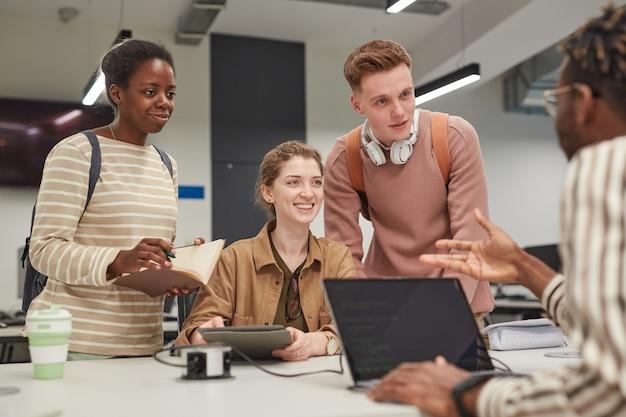 Разнообразная группа студентов обсуждает проект за столом, работая вместе в школьной библиотеке и весело улыбаясь