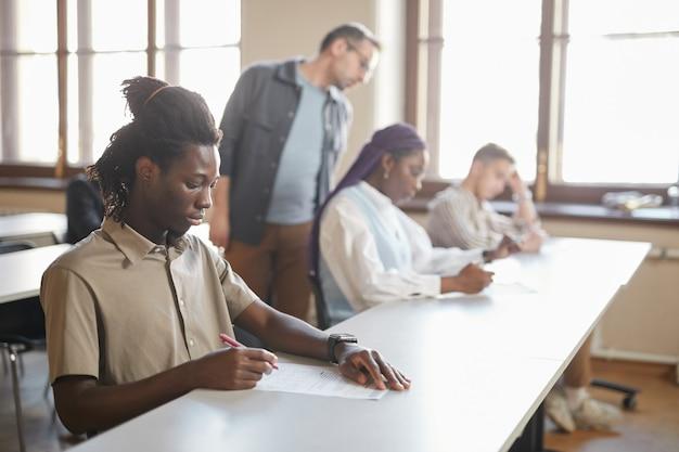 講堂の机に並んで座って大学で試験を受ける学生の多様なグループは、前景の若いアフリカ系アメリカ人の男性に焦点を当て、スペースをコピーします