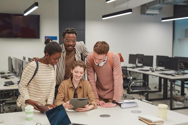 Разнообразная группа студентов, работающих вместе и использующих цифровой планшет, стоя за столом в школьной ит-лаборатории, копируя пространство
