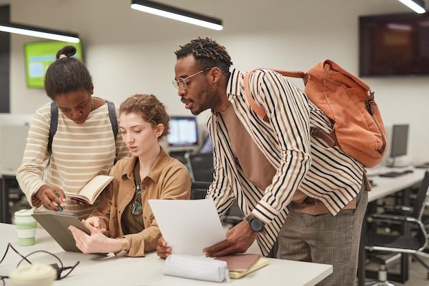 Разнообразная группа студентов, работающих вместе в современной школьной библиотеке и использующих цифровой планшет