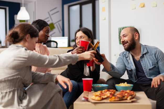 オフィスミーティングパーティーで仕事を終えて楽しんでいる多様な労働者のグループ。陽気な友達は、ビジネスからの休憩を祝うためにボトルとビールのカップを応援します。笑顔の多民族