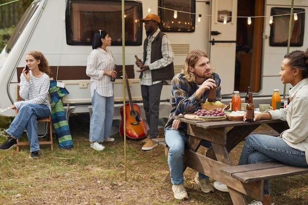 森のコピースペースでバンとキャンプしながら屋外でリラックスする若者の多様なグループ