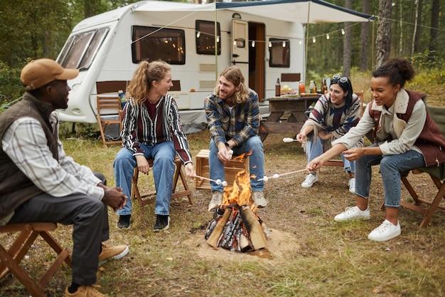 森の中で友達とキャンプを楽しみながらマシュマロを焼く若者たちの多様なグループ...
