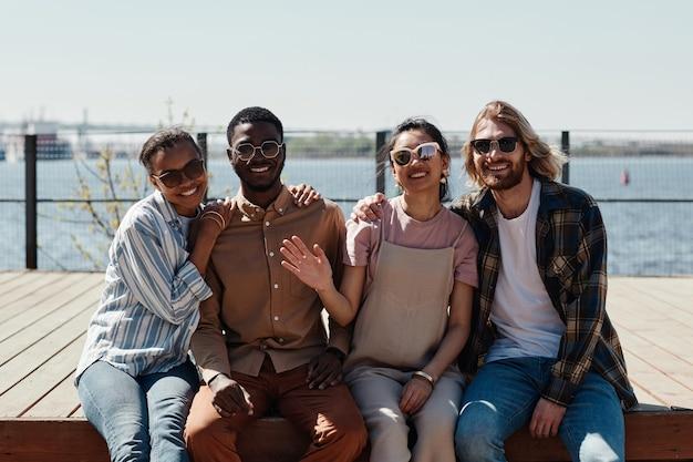 선글라스를 끼고 강가에서 야외 포즈를 취하면서 카메라를 보며 웃고 있는 다양한 젊은이들