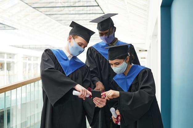 大学のインテリア、コピースペースで屋内で自分撮りをする卒業式のガウンとマスクを身に着けている若者の多様なグループ