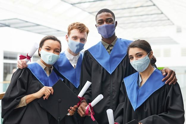Разнообразная группа молодых людей в выпускных платьях и масках, глядя в камеру в помещении в интерьере колледжа
