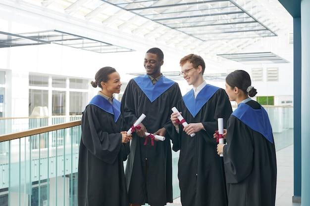 現代の大学のインテリアで屋内で楽しくおしゃべりする卒業式のガウンを着ている若者の多様なグループ