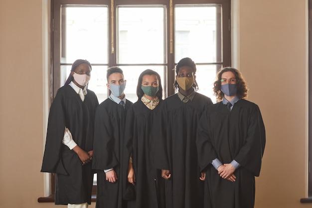 Разнообразная группа молодых людей в масках и черных церемониальных халатах во время выпускной церемонии в условиях пандемии коронавируса