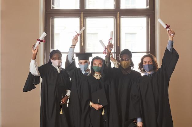 Разнообразная группа молодых людей в масках и черных церемониальных халатах во время выпускной церемонии в помещении в условиях пандемии коронавируса