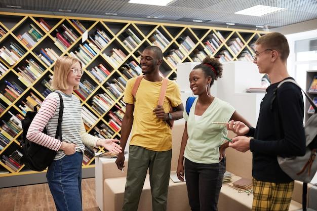 Разнообразная группа молодых студентов, встречающихся в библиотеке колледжа и улыбающихся