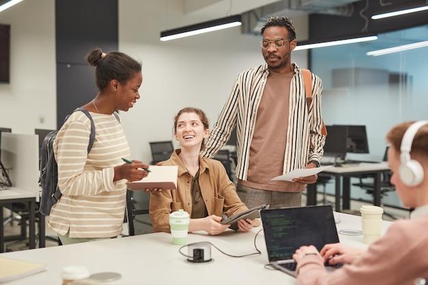 Разнообразная группа молодых студентов вместе используют ноутбук и весело болтают, работая над школьным проектом в колледже, скопируйте пространство