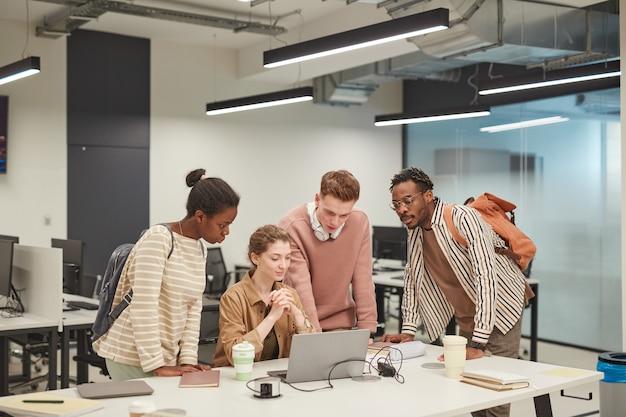 Разнообразная группа молодых студентов, совместно использующих ноутбук во время работы над школьным проектом в колледже, копирует пространство
