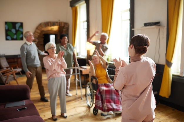Diverse group of smiling senior people dancing while enjoying activities in retirement home with you...