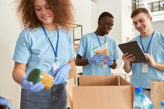 다양한 남자 자원 봉사자가 함께 일하는 음식 분류 및 포장을 계산하면서 웃고 있습니다.