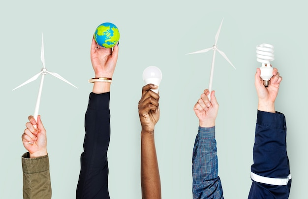 Diverse hands holding sustainable energy objects