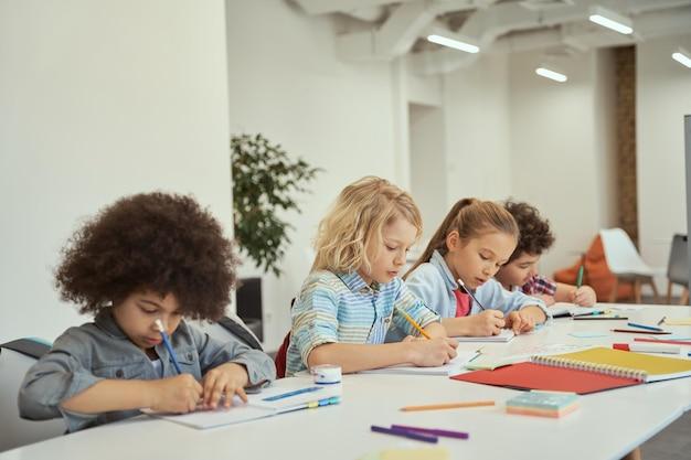 Разнообразные дети маленькие школьники делают заметки во время учебы, сидя за столом в