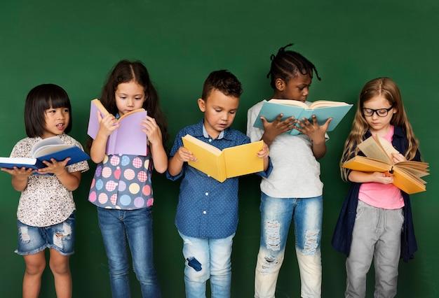 Bambini diversi che leggono libri