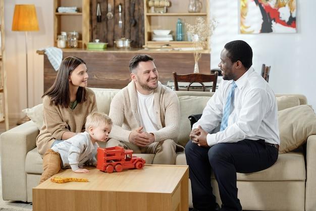 Разнообразный мужчина и счастливая семья с мальчиком, имеющим консультацию по недвижимости, сидя вместе на диване