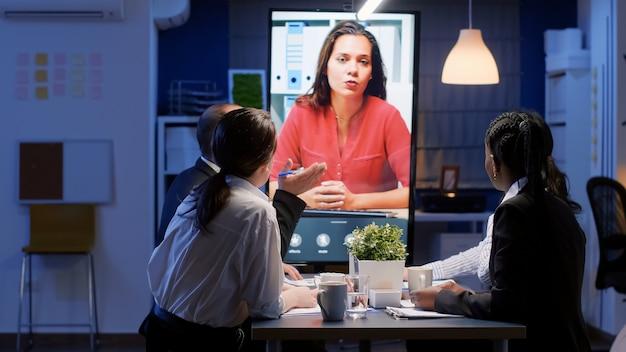 다양한 다민족 비즈니스 팀워크가 늦은 밤 사무실에서 금융 기업 전략에서 일하는 온라인 화상 회의 회의를 합니다. 회사 아이디어를 브레인스토밍하는 집중된 동료