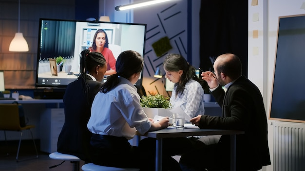 Diverse multi ethnic businesspeople discussing with remote entrepreneur during online videocall conference late at night in meeting office room. focused teamwork brainstorming ideas