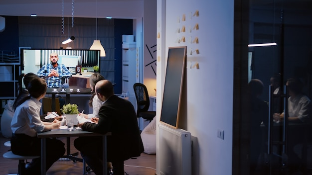 다양한 다민족 사업가들이 회사 사무실에서 늦은 밤 온라인 화상 통화 회의 중에 휠체어를 타고 원격 관리자와 토론합니다. 초과 근무에 집중하는 팀워크