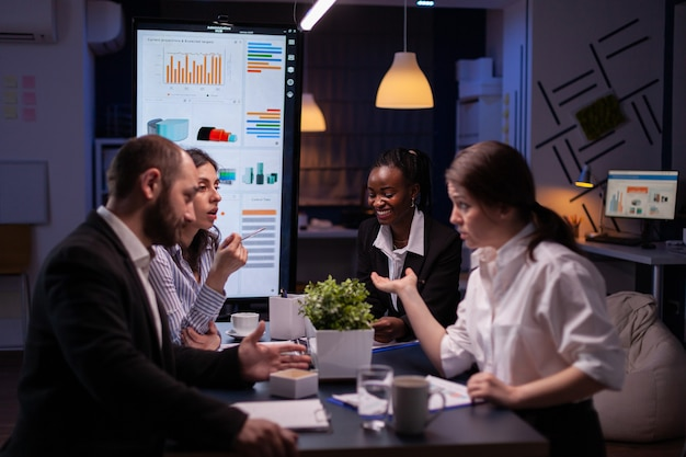 Diverse multiethnic businesspeople analyzing management strategy working overtime