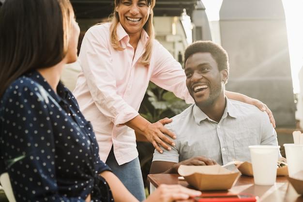 屋外のフードトラックレストランで食べる多様な人々-アフリカ系アメリカ人の男性の顔にソフトフォーカス