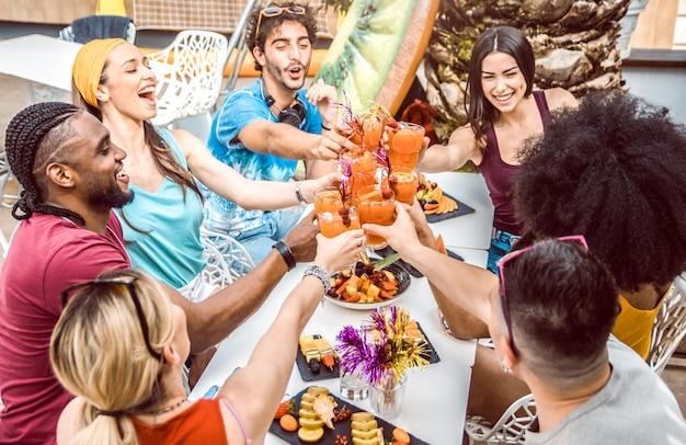 Разные люди друзья тусуются и пьют коктейли на открытом воздухе