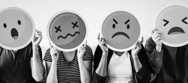 Diverse people holding emoji icons