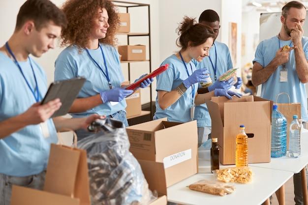 보호 장갑을 낀 다양한 사람들이 자원 봉사를 하는 판지 상자에 포장 식품을 분류합니다.