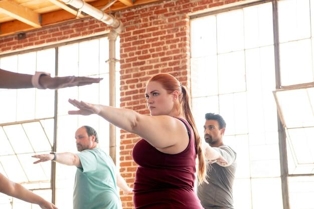 Разные люди практикуют позу йоги вирабхадрасана