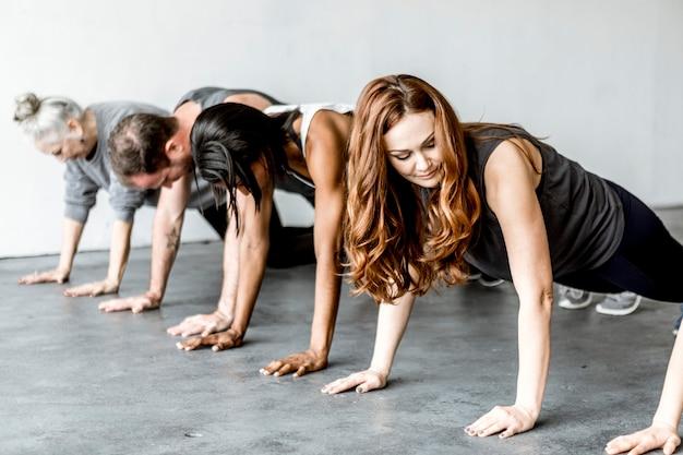 Diverse people practicing a phalakasana pose
