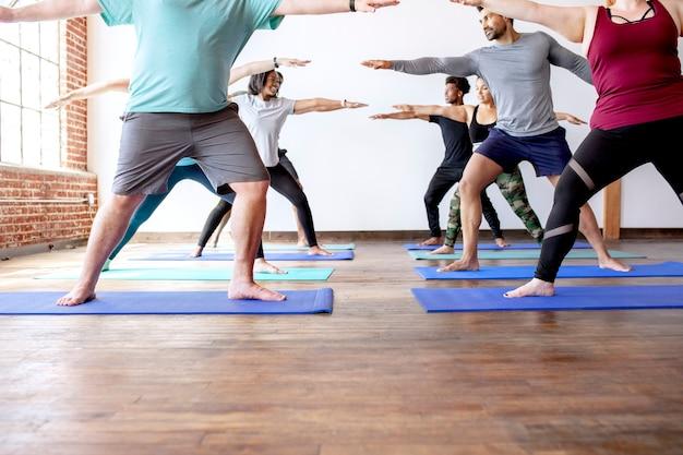 Diverse people practicing a virabhadrasana yoga pose