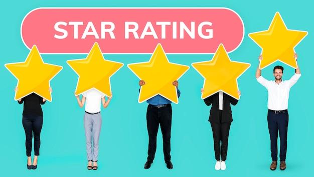 Разнообразные люди, показывающие символ золотой звезды рейтинга