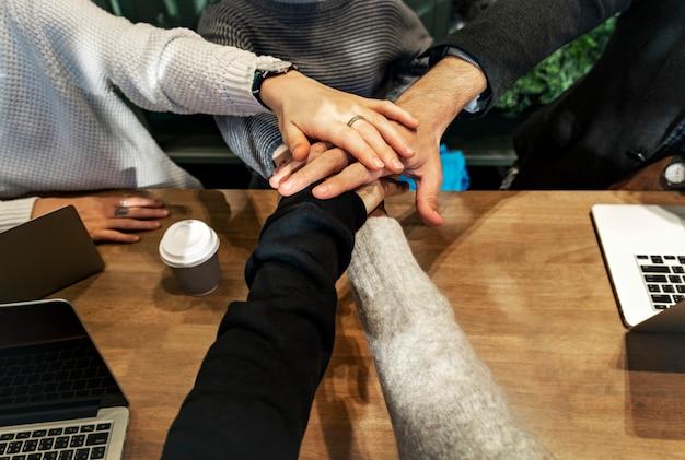 Diverse persone che impilano le mani insieme